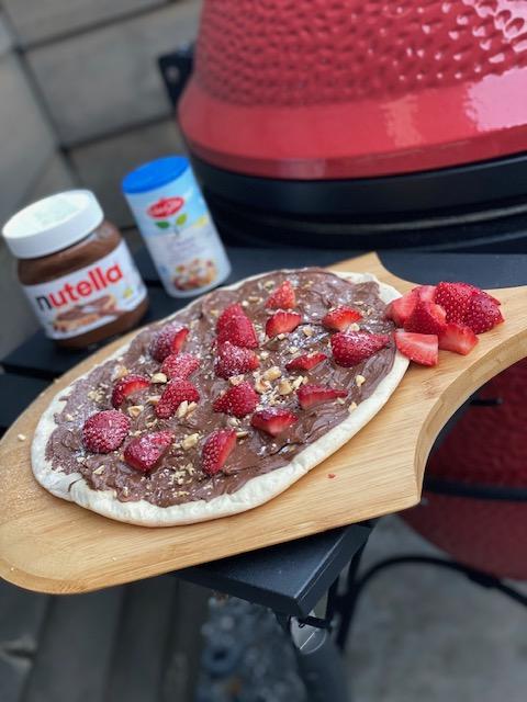 Nutella Pizza met verse aardbeien, fijngehakte hazelnoten en poedersuiker .